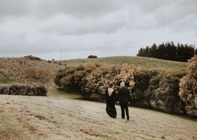 Wedding couple strolling in the paddock at Waipuna Wedding Venue
