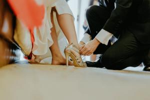 Groom doing up brides shoe