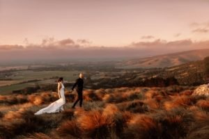 Bride and groom walking through tussock in the hills at dusk