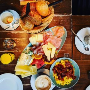 Breakfast spread of cheeses, eggs, bacon and breads