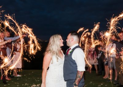 Bride and groom surrounded by sparklers at night
