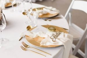 Table setting with gold charger plater gold cutlery, white napkin and gold place name